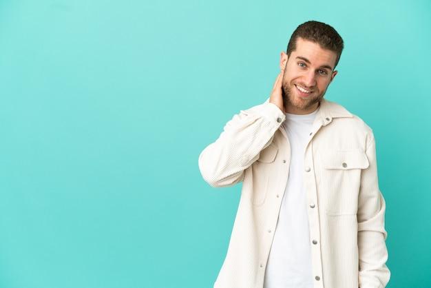 Homem loiro bonito sobre fundo azul isolado rindo