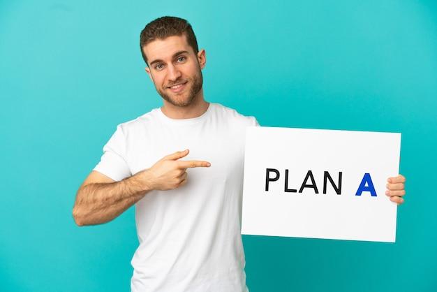Homem loiro bonito sobre fundo azul isolado segurando um cartaz com a mensagem plano a e apontando-o