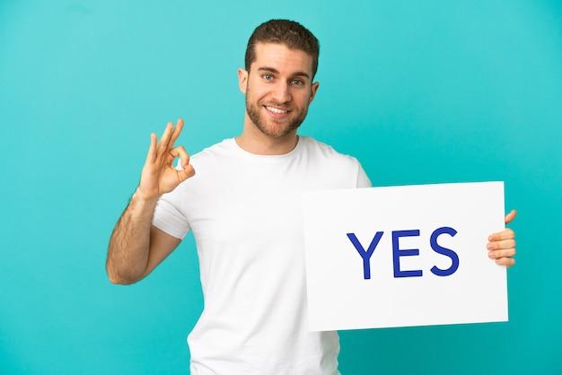 Homem loiro bonito sobre fundo azul isolado segurando um cartaz com o texto sim