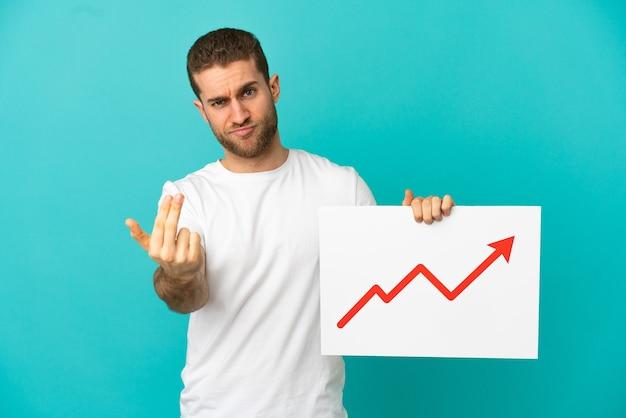 Homem loiro bonito sobre fundo azul isolado segurando uma placa com um símbolo de seta de estatísticas crescentes e fazendo o gesto de vinda