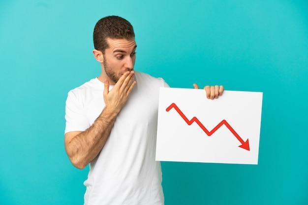 Homem loiro bonito sobre fundo azul isolado segurando uma placa com um símbolo de seta decrescente de estatísticas com expressão de surpresa
