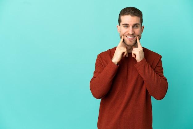 Homem loiro bonito sobre fundo azul isolado sorrindo com uma expressão feliz e agradável