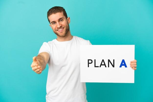 Homem loiro bonito sobre um fundo azul isolado segurando um cartaz com a mensagem plano a fazendo um acordo