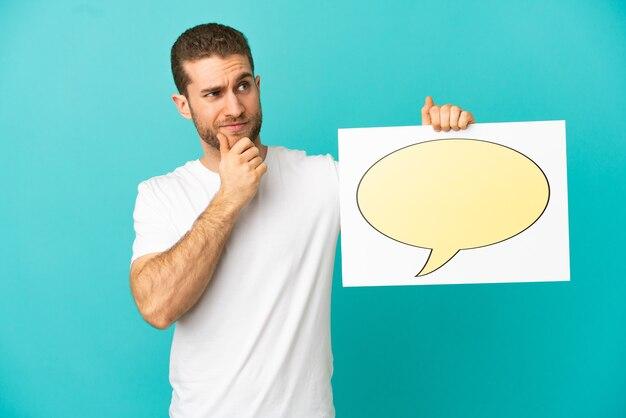 Homem loiro bonito sobre um fundo azul isolado, segurando um cartaz com o ícone de balão de fala e pensando