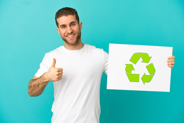 Homem loiro bonito sobre um fundo azul isolado, segurando um cartaz com o ícone de reciclagem com o polegar para cima