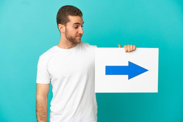 Homem loiro bonito sobre um fundo azul isolado segurando um cartaz com o símbolo de seta