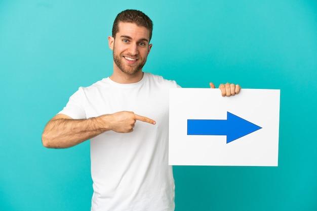 Homem loiro bonito sobre um fundo azul isolado segurando um cartaz com o símbolo de uma seta e apontando-o