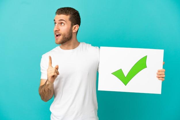 Homem loiro bonito sobre um fundo azul isolado segurando um cartaz com o texto ícone de marca de seleção verde e pensando