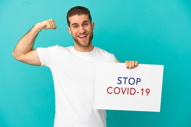 Homem loiro bonito sobre um fundo azul isolado segurando um cartaz com o texto pare covid 19 e fazendo um gesto forte