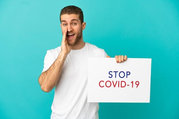 Homem loiro bonito sobre um fundo azul isolado segurando um cartaz com o texto pare covid 19 e gritando