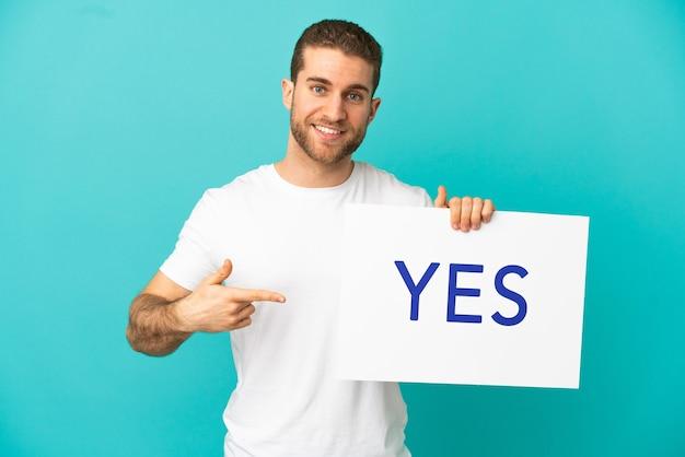 Homem loiro bonito sobre um fundo azul isolado segurando um cartaz com o texto sim e apontando-o
