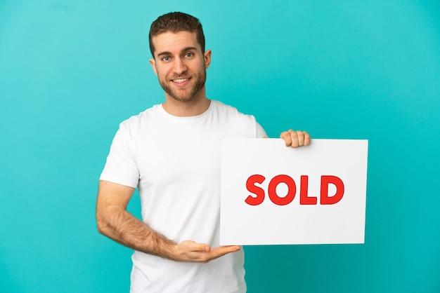 Homem loiro bonito sobre um fundo azul isolado segurando um cartaz com o texto vendido com uma expressão feliz