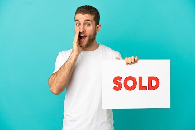 Homem loiro bonito sobre um fundo azul isolado segurando um cartaz com o texto vendido e gritando