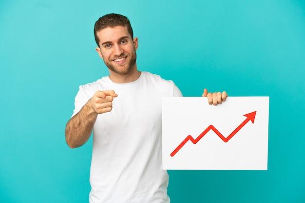 Homem loiro bonito sobre um fundo azul isolado segurando uma placa com um símbolo de seta de estatísticas crescentes e apontando para a frente