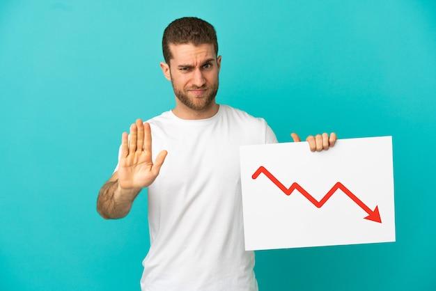 Homem loiro bonito sobre um fundo azul isolado, segurando uma placa com um símbolo de seta de estatísticas decrescentes e fazendo o sinal de pare