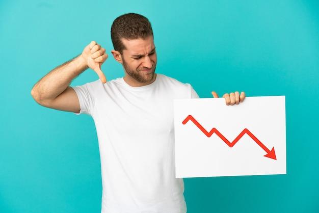 Homem loiro bonito sobre um fundo azul isolado segurando uma placa com um símbolo de seta decrescente de estatísticas e fazendo um sinal ruim
