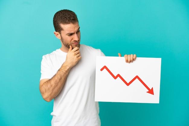 Homem loiro bonito sobre uma parede azul isolada segurando uma placa com um símbolo de seta de estatísticas decrescentes e pensando