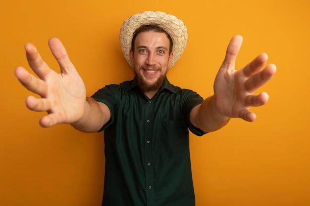Homem loiro bonito sorridente com chapéu de praia, estendendo as mãos isoladas na parede laranja