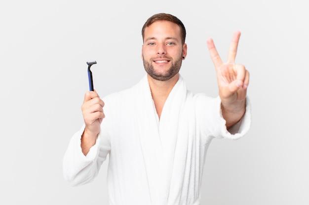 Homem loiro bonito sorrindo e parecendo feliz, gesticulando vitória ou paz. conceito de barbear