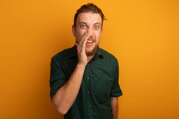 Homem loiro bonito surpreso com a mão perto da boca chamando alguém olhando para a câmera em laranja