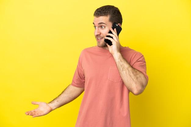 Homem loiro bonito usando telefone celular sobre fundo isolado com expressão de surpresa enquanto olha de lado