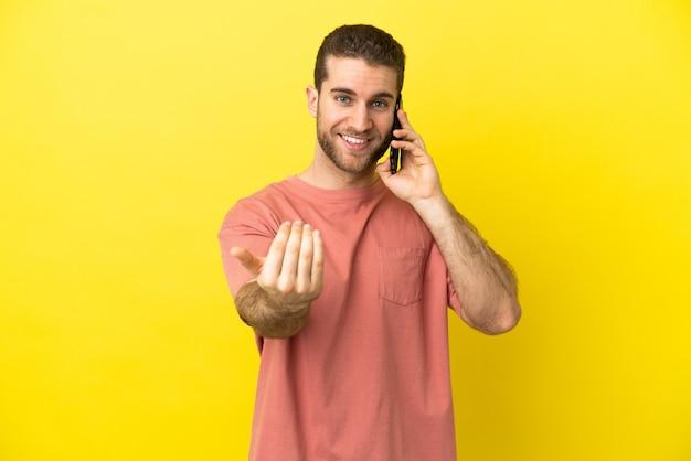 Homem loiro bonito usando telefone celular sobre fundo isolado, convidando para vir com a mão. feliz que você veio