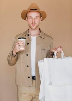Homem loiro com café e sacolas de compras