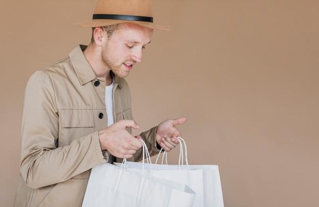 Homem loiro com chapéu marrom e redes de compras