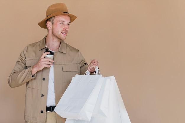 Homem loiro com sacolas de compras e café