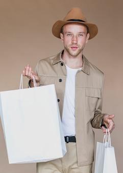Homem loiro com sacos de compras, olhando para a câmera
