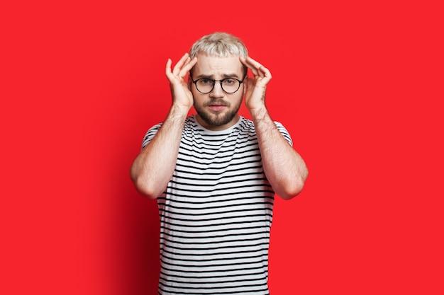 Homem loiro de óculos gesticulando com dor de cabeça na parede vermelha do estúdio, tocando sua cabeça