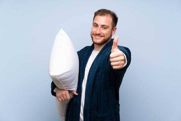 Homem loiro de pijama sobre parede azul com polegares para cima porque algo de bom aconteceu