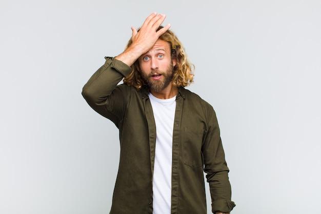 Homem loiro erguendo a palma da mão na testa pensando oops, depois de cometer um erro estúpido ou lembrar, sentindo-se bobo