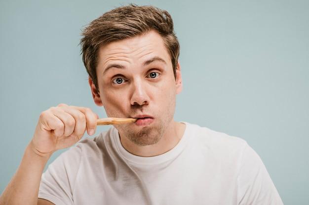 Homem loiro escovando os dentes com uma escova de madeira