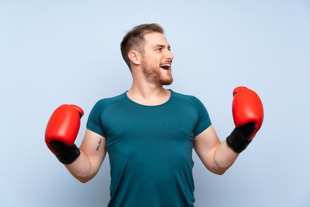 Homem loiro esporte parede azul com luvas de boxe