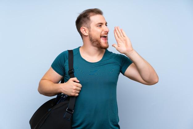 Homem loiro esporte parede azul gritando com a boca aberta