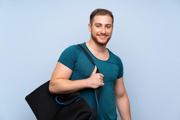 Homem loiro esporte parede azul sorrindo muito