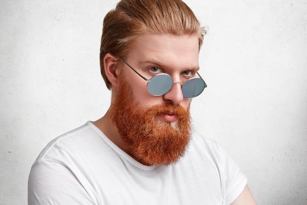 Homem loiro expressivo com barba ruiva e óculos escuros