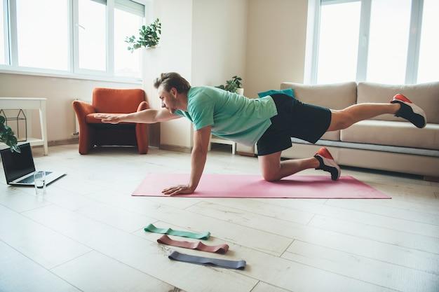 Homem loiro fazendo alongamento durante exercícios físicos em casa usando um laptop no chão