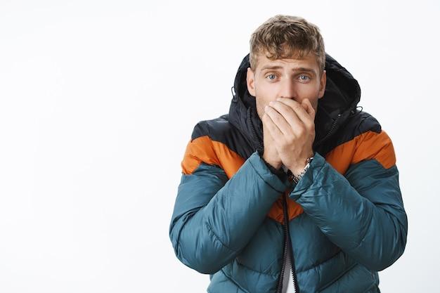 Homem loiro fofo e charmoso com olhos azuis exalando ar quente nas palmas das mãos perto da boca, levantando as sobrancelhas bobo como se estivesse tremendo de frio, congelando lá fora durante um dia de neve usando uma jaqueta acolchoada