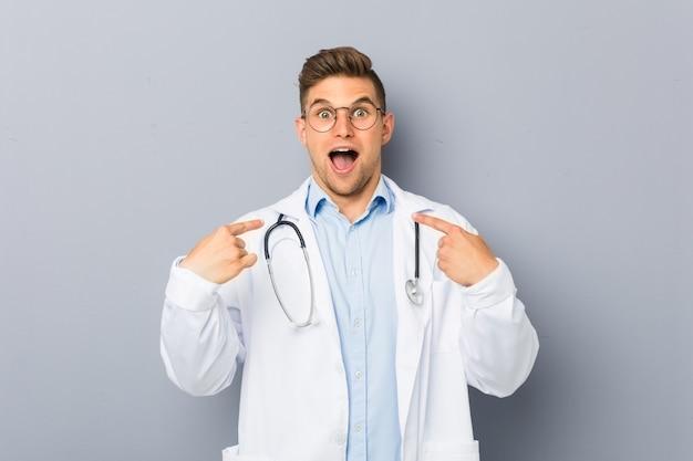 Homem loiro jovem médico surpreso apontando para si mesmo, sorrindo amplamente
