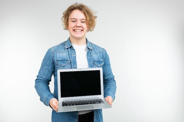 Homem loiro legal satisfeito segurando um laptop com um layout para inserir uma página em um fundo branco