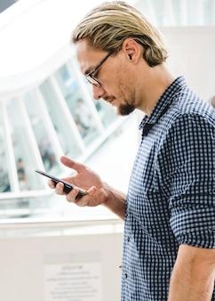 Homem loiro mensagens de texto em seu telefone