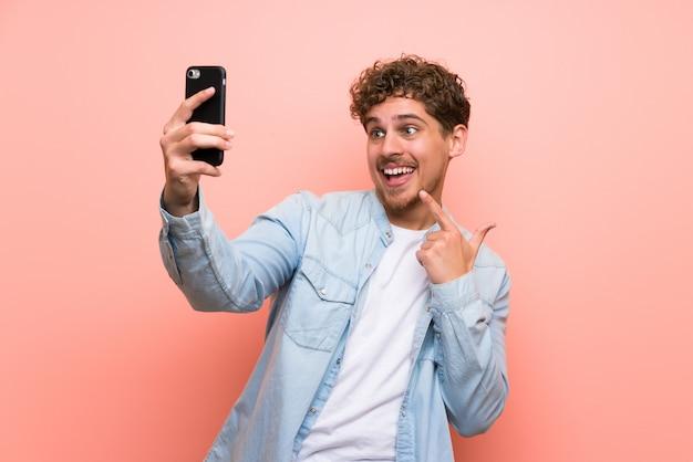 Homem loiro parede rosa fazendo uma selfie