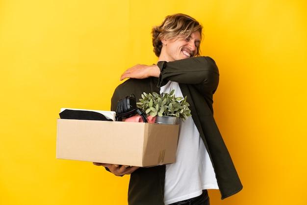 Homem loiro se mexendo enquanto apanha uma caixa cheia de coisas isoladas no fundo amarelo sofrendo de dor no ombro por ter feito esforço