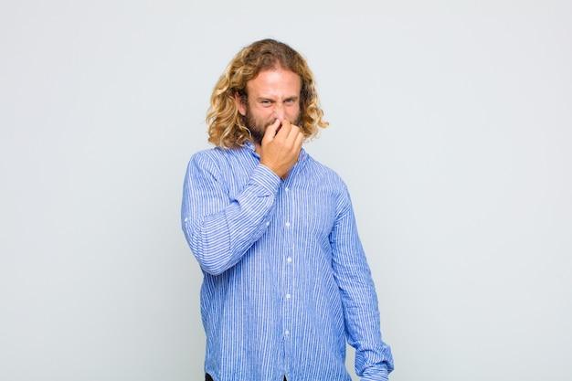 Homem loiro se sentindo enojado, segurando o nariz para evitar cheirar um fedor desagradável