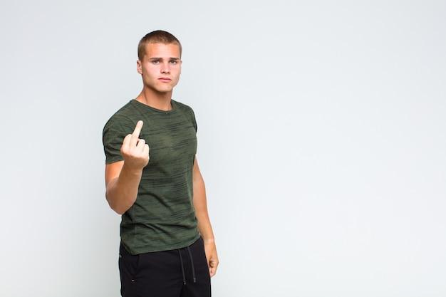 Homem loiro se sentindo zangado, irritado, rebelde e agressivo, sacudindo o dedo do meio e revidando