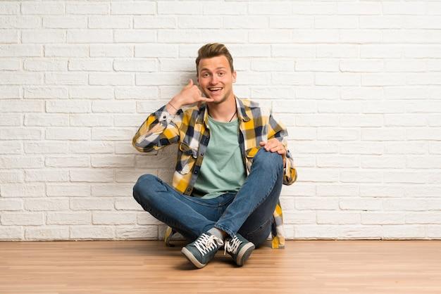Homem loiro sentado no chão fazendo gesto de telefone, me ligue de volta sinal
