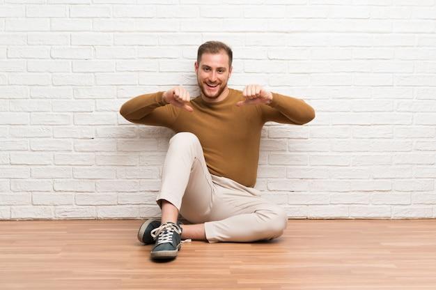 Homem loiro sentado no chão, orgulhoso e satisfeito