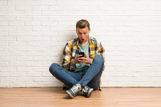 Homem loiro sentado no chão surpreso e enviando uma mensagem
